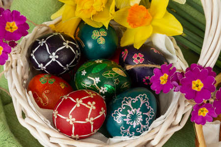 Easter eggs and Easter bun with flowers - green background