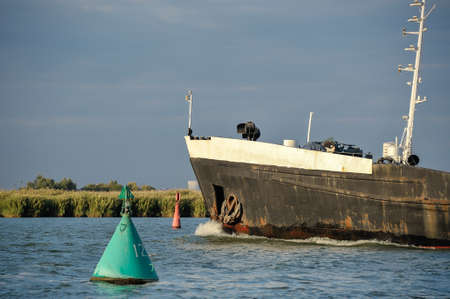 pied: A large ship passes the signal buoys on the fairway on the river
