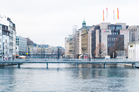 Geneva, Switzerland - December 24, 2016: Riverside buildings with offices of famous brands near Rhone river in city center of Geneva . It is a  a financial center and worldwide center for diplomacy