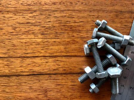 Schroeven, bouten en handgereedschap bij elkaar geplaatst op een bruine houten vloer Stockfoto