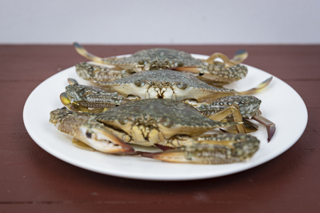 blue crabs on plate, on a wooden background