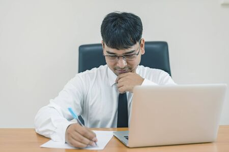 Young attractive businessman thinking, writing on paper and computer laptop at office