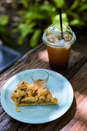 Apple pie with coffee on a wooden table in the garden
