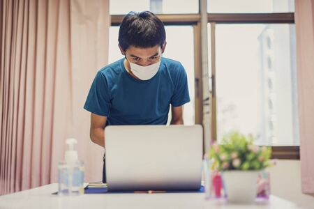 The man wear a mask to protect against the coronavirus covid-19, work from home with disinfectant gel.