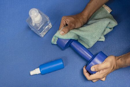 Clean exercise equipment by wiping with an alcohol gel to prevent Coronavirus, cover 19