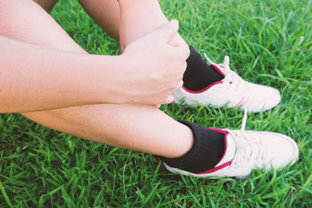 hugged: People hugged her knees on the grass green in relax time Stock Photo