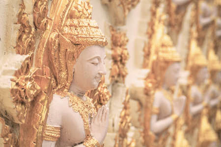 focus on foreground: Thailand idol statues in the temple at noon in film tone