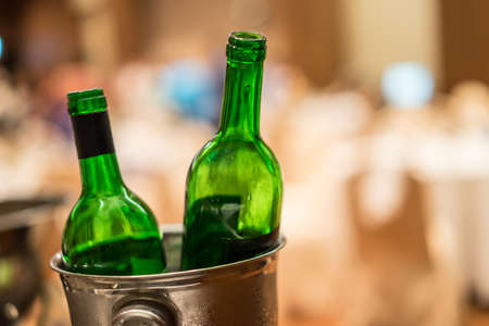 Green bottle placed in a bucket of silver in party.