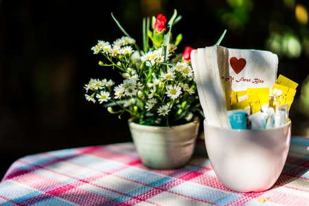 Flowers and a glass coffee table in the cafe in sunshine. Stock Photo