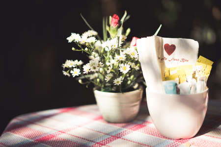 Flowers and a glass coffee table in the cafe in old sunshine. Stock Photo