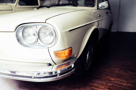 Old white vintage cars that have been preserved in the garage for a long time.