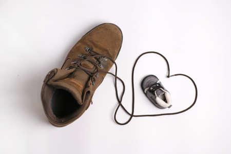 vater und baby: Zwei Schuhe, ein gro�er, eine kleine, mit Herz