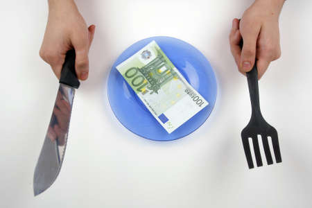 One hundred euro bill on a plate, with hands holding a knife and a fork photo