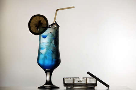 ashtray: A blue cocktail, an ashtray and a cigarette