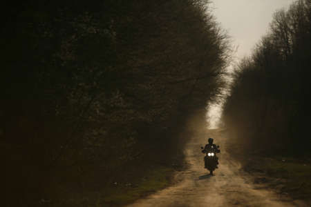 motorcycle racing: A motorcycle and its rider are silhouetted on an off-road track in Romania Stock Photo