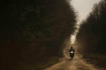silueta moto: Una moto y su jinete se perfilan en una pista de todoterreno en Rumania Foto de archivo