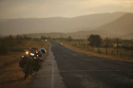 Motorcycle on a straight road at dusk Stock Photo