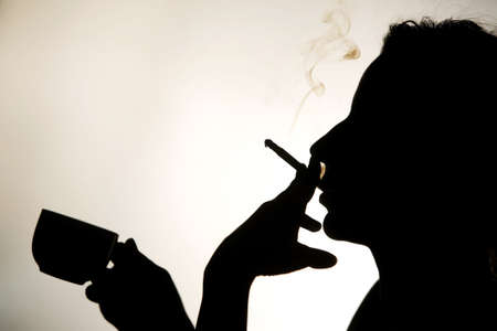Silhouette of a woman smoking a cigarette and drinking a coffee Stock Photo - 9385520