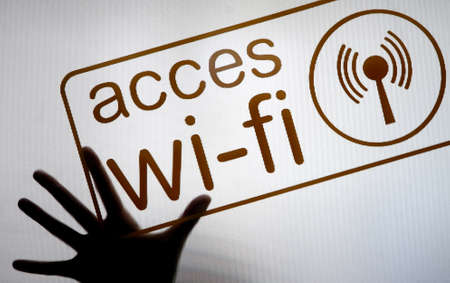 A hand pressed against a diffused screen with a WiFi sign photo