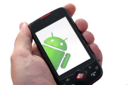 Bucharest, Romania - June 21, 2011: Close-up shot of a hand holding an Android smartphone with the Android logo displayed on the screen. Android is a software stack for mobile devices that includes an operating system, middle-ware and key applications.  Stock Photo - 9890800