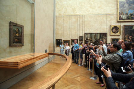 Paris, France - May 20, 2011: Visitors at the Louvre museum in Paris take pictures of the Mona Lisa portrait. Mona Lisa is a portrait painted in oil on a poplar panel by the Florentine artist Leonardo da Vinci.