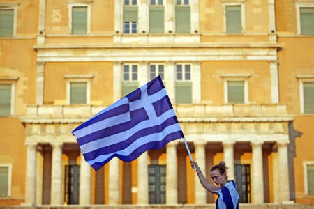 Athens, Greece - June 30, 2011: A Greek woman holds a flag in front of the Greek parliament during a protest in Athens, Greece.