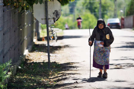 Dolhesti, Romania - September 9, 2011: An elderly woman walks down a street in Dolhesti, Romania.