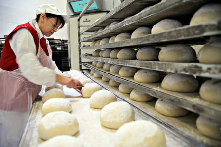 panettiere: Bucharest, Romania - 19 dicembre 2011: Donna cottura del pane in un forno a Bucarest, Romania.