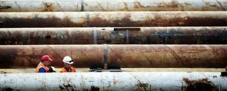 Bucharest, Romania - September 20, 2011: Workers at a construction site check giant tubes. Stock Photo - 11748897