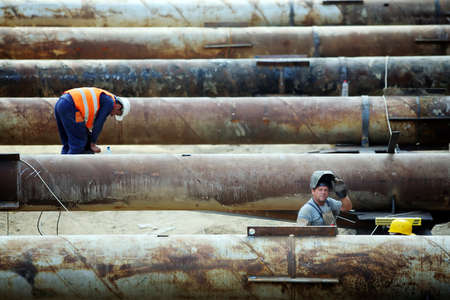 Bucharest, Romania - September 20, 2011: Workers at a construction site check giant tubes.