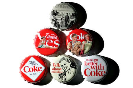 cola bottle: Bucharest, Romania - November 29, 2011: Five vintage Coca-Cola bottle caps, 125 years old anniversary edition, studio shot.