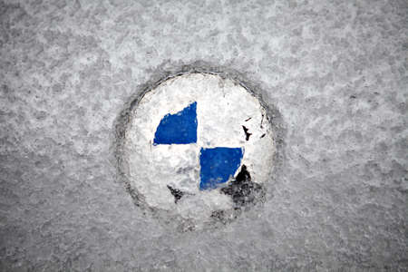 driving conditions: Bucharest, Romania - February 5, 2012: Picture of the BMW logo covered with ice. Founded in 1917, Bayerische Motoren Werke AG is a German automobile, motorcycle and engine manufacturing company.