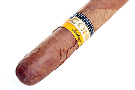 Bucharest, Romania - February 28, 2012: Detail of an old Cohiba Cuban cigar isolated on white. Cohiba is a brand for two kinds of premium cigar produced in Cuba and in the Dominican Republic for US-based General Cigar Company.