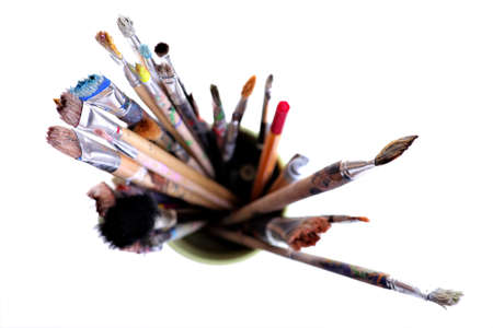 Various dirty paint brushes in a jar with shallow depth of field photo
