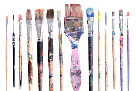 Various dirty paint brushes displayed side by side