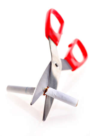 Studio shot of a pair of scissors cutting a cigarette, metaphor for quitting smoking  photo