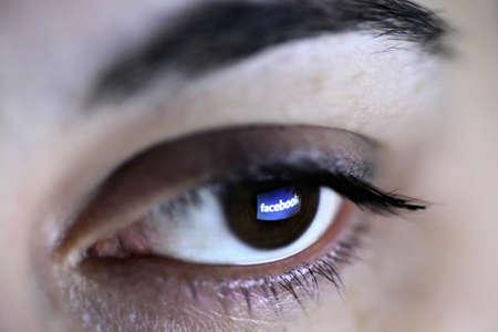 marca libros: Bucarest, Rumania - 27 de marzo de 2012: logotipo de Facebook se refleja en un ojo. Facebook es una red social lanzada en febrero de 2004, con m�s de 845 millones de usuarios activos.