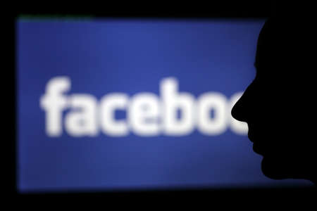 marca libros: Bucarest, Rumania - 27 de marzo de 2012: Un rostro humano se recorta contra una pantalla que muestra el logotipo de Facebook. Facebook es una red social lanzada en febrero de 2004, con m�s de 845 millones de usuarios activos.