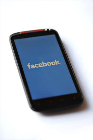 social networking service: Bucarest, Rumania - 28 de marzo de 2012: logotipo de Facebook se muestra en una pantalla de tel�fono m�vil. Facebook es una red social lanzada en febrero de 2004, con m�s de 845 millones de usuarios activos. Editorial