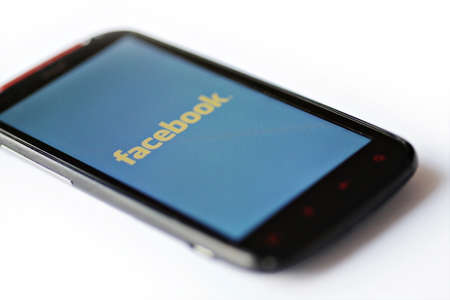 Bucharest, Romania - March 28, 2012: Facebook logo is displayed on a mobile phone screen. Facebook is a social networking service launched in February 2004, having more than 845 million active users. Stock Photo - 12993600