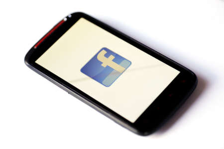 Bucharest, Romania - March 28, 2012: Facebook logo is displayed on a mobile phone screen. Facebook is a social networking service launched in February 2004, having more than 845 million active users. Stock Photo - 13062545