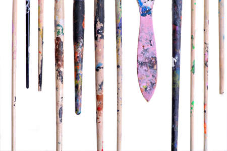 Various dirty paint brushes ends displayed side by side photo