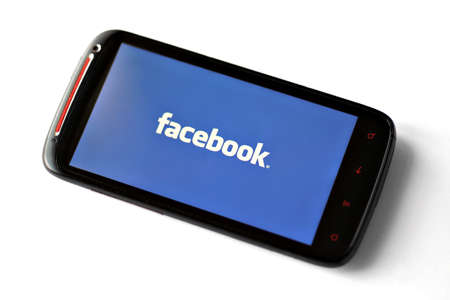 web surfing: Bucharest, Romania - March 28, 2012: Facebook logo is displayed on a mobile phone screen. Facebook is a social networking service launched in February 2004, having more than 845 million active users.
