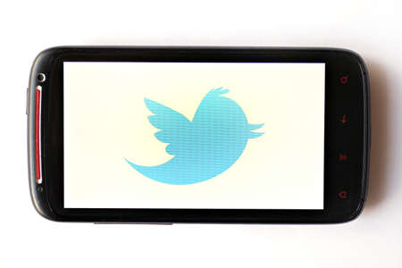 tweeting: Bucharest, Romania - March 28, 2012: Twitter logo is displayed on a mobile phone screen. Twitter is an online social networking service and microblogging service that enables its users to send and read text-based posts. Editorial