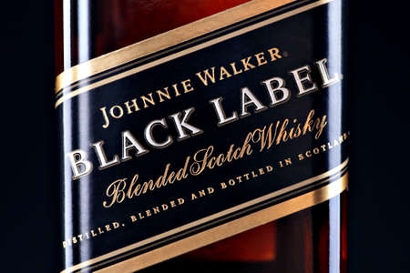 owned: Bucharest, Romania - April 17, 2012: Close-up shot of a bottle of Johnnie Walker whiskey. Johnnie Walker is a brand of Scotch Whisky owned by Diageo and originated in Kilmarnock, Ayrshire, Scotland.
