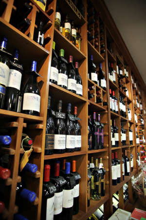 wood trade: Bucharest, Romania - May 31, 2012: Wine bottles are displayed on shelves in a store in Bucharest, Romania.