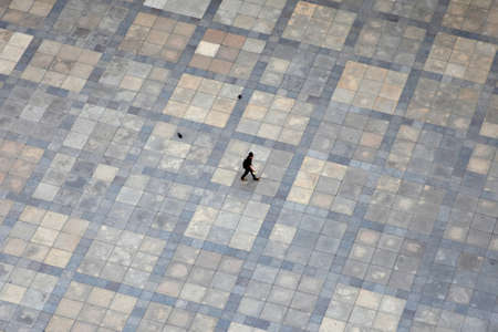 pictured: Prague, Czech Republic - July 3, 2012: A lonely tourist is pictured from above while traversing the square in front of St.Vitus Cathedral in Prague, Czech Republic.
