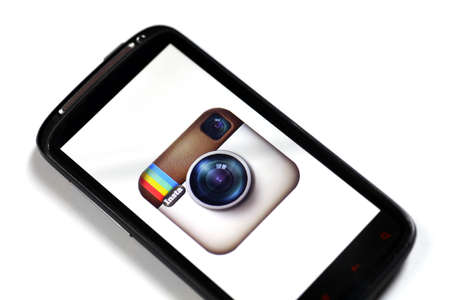 Bucharest, Romania - June 23, 2012: Close up shot of a smartphone displaying the Instagram logo on its screen, using a picture viewing software. Instagram is a free photo-sharing program and its distinctive feature is that it takes square shape photos tha