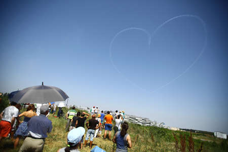 Bucharest, Romania - July 21, 2012: People watch planes drawing a heart in the sky during the Bucharest International Air Show 2012, at Baneasa airport, in Bucharest, Romania.