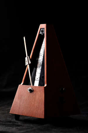 Vertical shot of a vintage metronome isolated on white photo